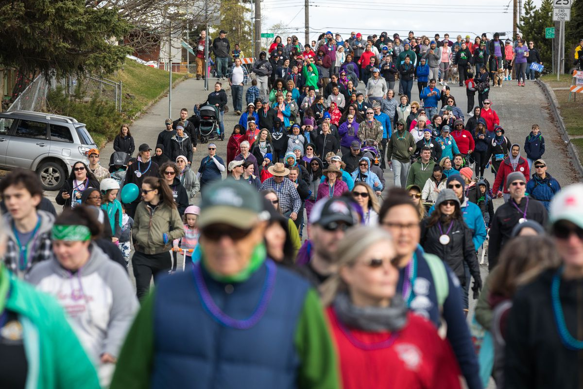 Participants in the Out of Darkness Community Walk make their way down N Street on Saturday at Delaney Park. Organizers with the American Foundation for Suicide Prevention said hundreds of people participated in the eighth annual walk. (Loren Holmes / ADN)