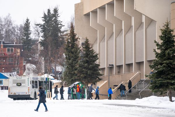 People get off a bus at a temporary homeless shelter, setup in the Sullivan Arena, on Saturday, March 21, 2020. The Municipality of Anchorage is converting both the Sullivan Arena and Ben Boeke Ice Arena into emergency homeless shelters, which will allow for people to sleep at least 6 feet apart in the hopes of controlling the transmission of COVID-19. (Loren Holmes / ADN)