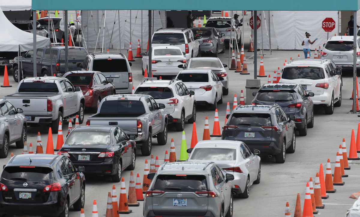 Vehicles wait in line at a drive-thru COVID-19 testing site outside Hard Rock Stadium, Wednesday, July 8, 2020, in Miami Gardens, Fla. (AP Photo/Wilfredo Lee)