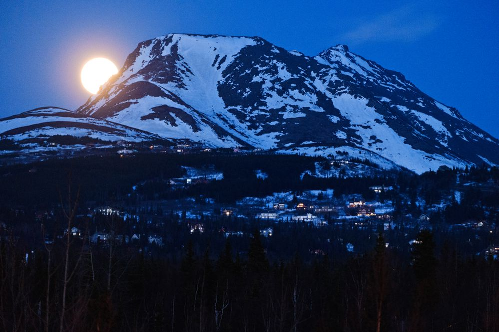 The full moon rises into view from the Anchorage Hillside near Flattop Mountain on April 26, 2021. (Marc Lester / ADN)