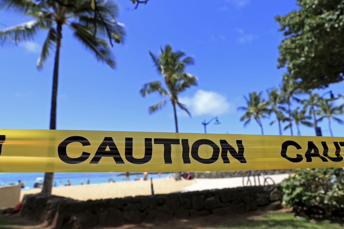 With beachgoers in the background, yellow caution tape is wrapped across an area of Waikiki, Friday, March 20, 2020, in Honolulu. Honolulu closed all public parks and recreation areas Friday until the end of April in an effort to help stop the spread of the coronavirus. (AP Photo/Marco Garcia)
