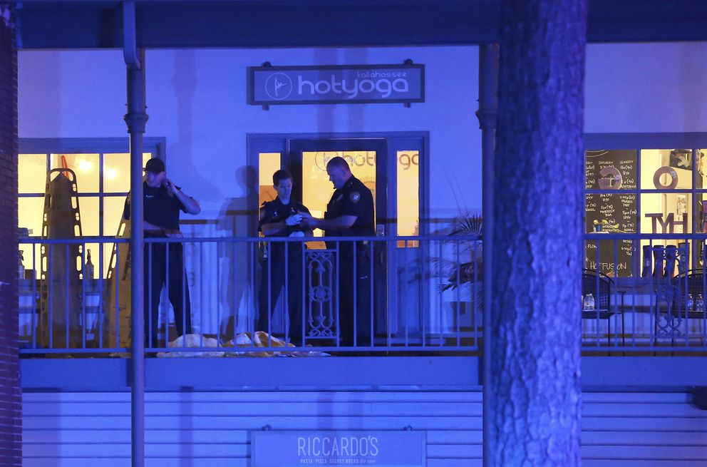 Police investigators work the scene of a shooting, Friday, Nov. 2, 2018, in Tallahassee, Fla. A shooter killed one person and critically wounded four others at a yoga studio in Florida's capital before killing himself. (AP Photo/Steve Cannon)