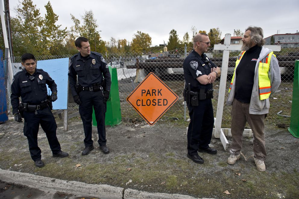 Anchorage Police Sgt. Cam Hokenson talks with Ron Alleva at right as other officers stand by. (Marc Lester / Alaska Dispatch News)