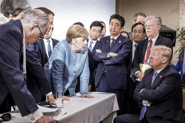 **EDS.: RETRANSMISSION OF XNYT108 SENT 6-9-2018 TO ADD ADDITIONAL NAMES** German Chancellor Angela Merkel speaks to President Donald Trump during the second day of the G-7 summit meeting in La Malbaie, Quebec, Canada, June 9, 2018. From left: Larry Kudlow, director of the National Economic Council; British Prime Minister Theresa May; French President Emmanuel Macron; Merkel; Japanese Prime Minister Shinzo Abe; John Bolton, the United States national security adviser; and Trump. (Jesco Denzel/Bundesregierung via The New York Times) -- FOR EDITORIAL USE ONLY --