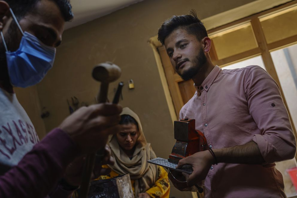 Muhammad Haidar, 22, a jewelry maker, right, works on making new jewelry at a store in Mandawi Market in Kabul, Afghanistan, on October 19, 2020. Haidar wants to leave for the United States or Canada, or almost any place where he can make a living selling his handmade silver earrings and lapis stone pendants. Trained in his craft by a British-funded nongovernmental organization, he and his two partners made more than $30,000 between 2016 and 2019, selling their jewelry, mostly to aid workers and diplomats in Kabul. (Marcus Yam/Los Angeles Times/TNS)