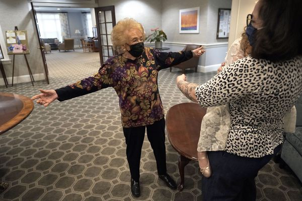 Gloria Winston, 94, left, a resident at Laurelmead Cooperative retirement community, in Providence, R.I., reaches out to hug her great-niece Wensday Greenbaum, right, and her 5-year-old great-great niece Cordelia Cappelano, behind right, at the retirement community, Thursday, March 18, 2021, in Providence. Before the pandemic, the two would often join Winston for lunch or swim in the building's pool. Greenbaum said they've visited a few times since, but always outside and always at a safe distance. (AP Photo/Steven Senne)