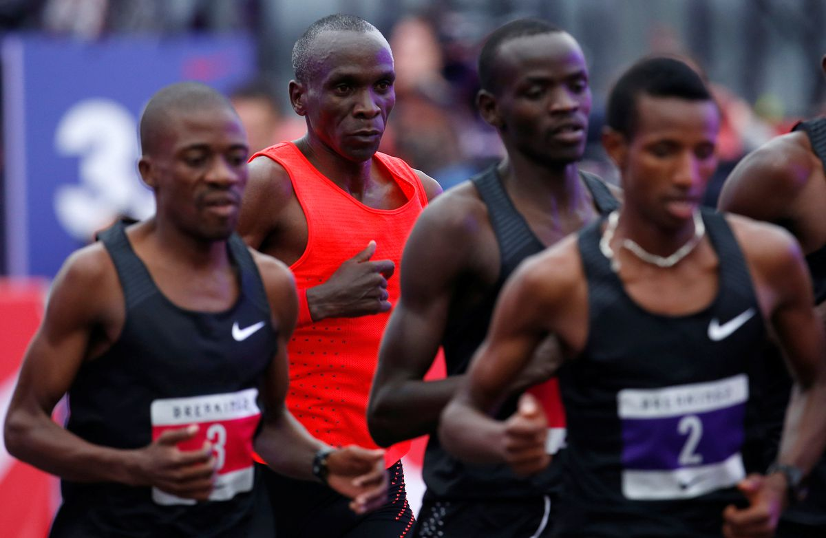 86e8df2a2417 Kenyan Eliud Kipchoge (in red) runs behind pacers during an attempt to break  the