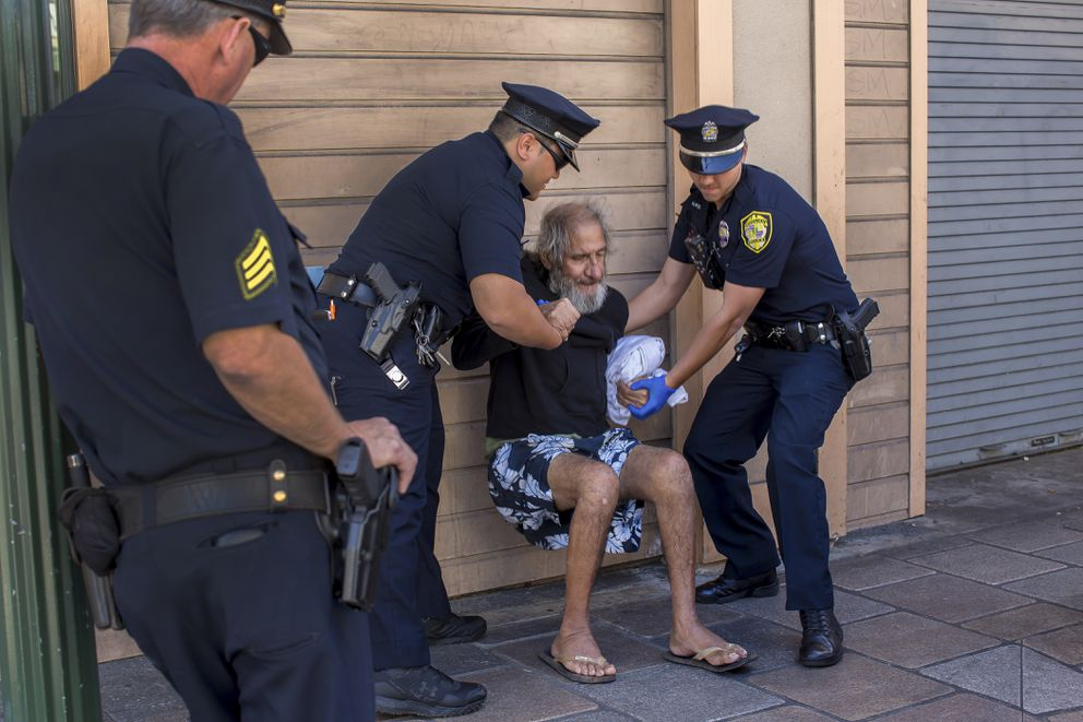 Honolulu police lift Larry Cutler, who was sitting on the sidewalk in Honolulu's Chinatown district, before walking him to a bus stop where he can legally sit. (Monica Almeida/The New York Times)