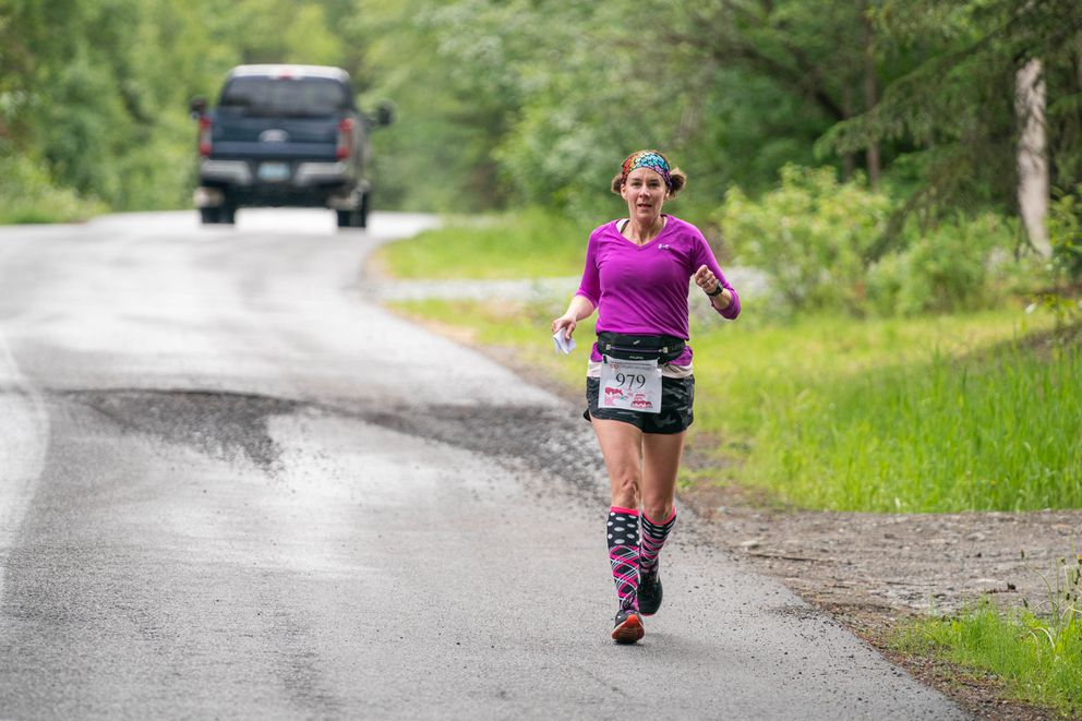 Renae Werner, carrying a race map in one hand, runs down a hill on the challenging 5-mile course. (Loren Holmes / ADN)