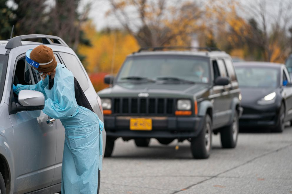 Kia Hasson collects a sample at a drive-through COVID-19 testing site operated by Visit Healthcare on Friday, Oct. 2, 2020 at the Loussac Library in Anchorage. (Loren Holmes / ADN)
