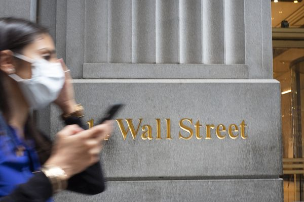 A woman wearing a mask passes a sign for Wall Street, Tuesday, June 30, 2020, during the coronavirus pandemic. (AP Photo/Mark Lennihan)