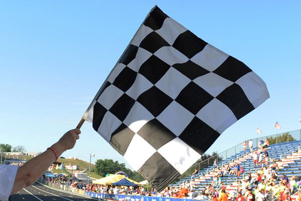 Janet Schroeter waves the checkered flag at the end of an elimination race during the 77th annual All-American Soap Box Derby in Akron, Ohio on Saturday, July 26, 2014. (AP Photo/David Dermer)