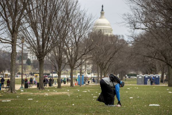 FILE - In this Dec. 25, 2018, file photo, the Capitol building is visible as a man picks up garbage during a partial government shutdown on the National Mall in Washington. No city experiences a shutdown quite like Washington. Besides the economic impact, a shutdown warps the nation's capital on a cultural, recreational and logistical level. (AP Photo/Andrew Harnik, File)