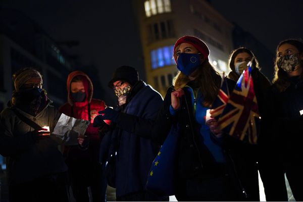British citizens, who live in Belgium, hold candles and Union flags during an anti Brexit vigil in front of the UK mission building at the European quarter in Brussels, Thursday, Dec. 31, 2020. At 11pm London time, midnight at EU headquarters in Brussels, Britain economically and practically left the 27-nation bloc, 11 months after its formal political departure. (AP Photo/Francisco Seco)