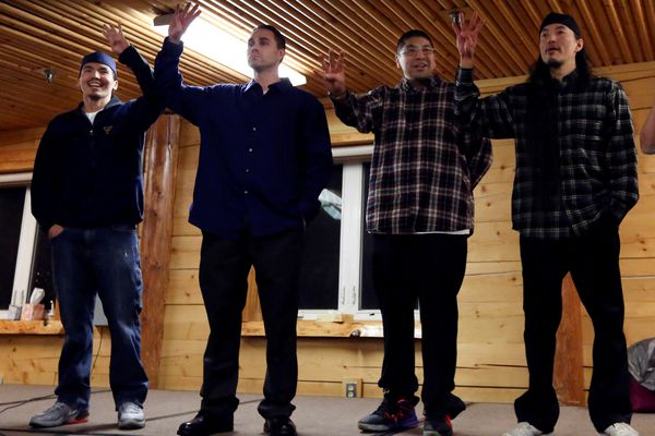 Pictured: The Fairbanks Four, left to right: Marvin Roberts, Kevin Pease, Eugene Vent, and George Frese, hold up four fingers, symbolizing the Fairbanks Four, in the David Salmon Tribal Hall after they were freed on Thursday, Dec. 17, 2015 in Fairbanks, Alaska.