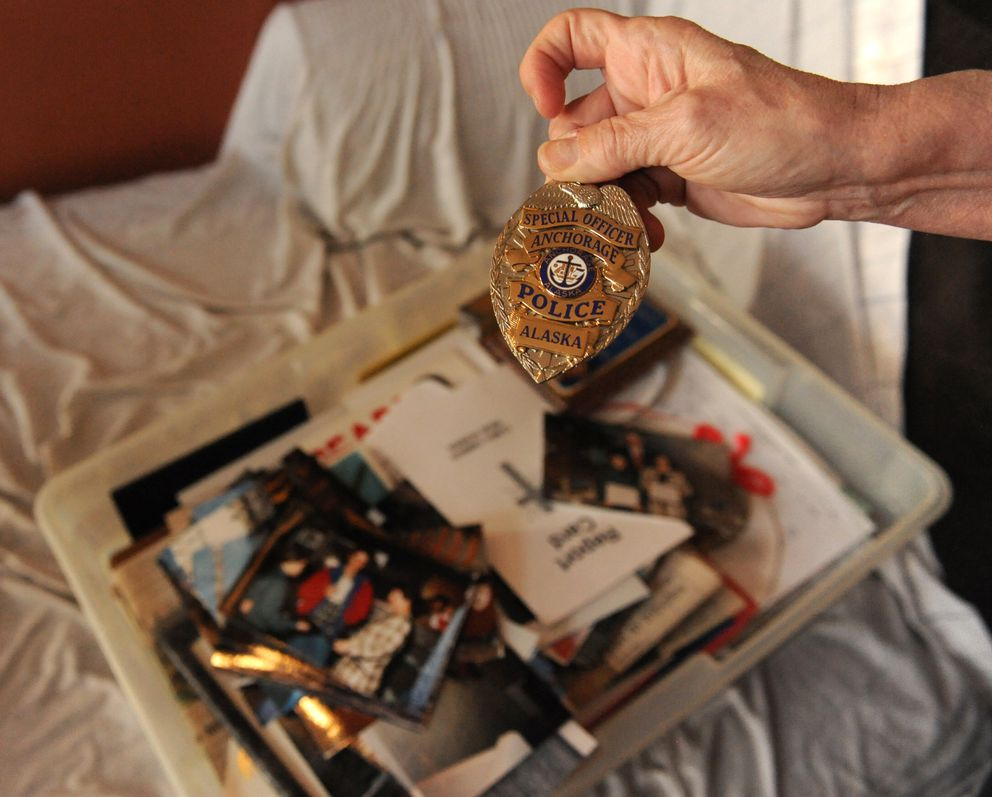 Debbie Cargill looks at an APD police badge that was presented to her son, David Cargill, when he was a boy. The box is full of mementos of David and Debbie's lives. (Anne Raup / ADN)