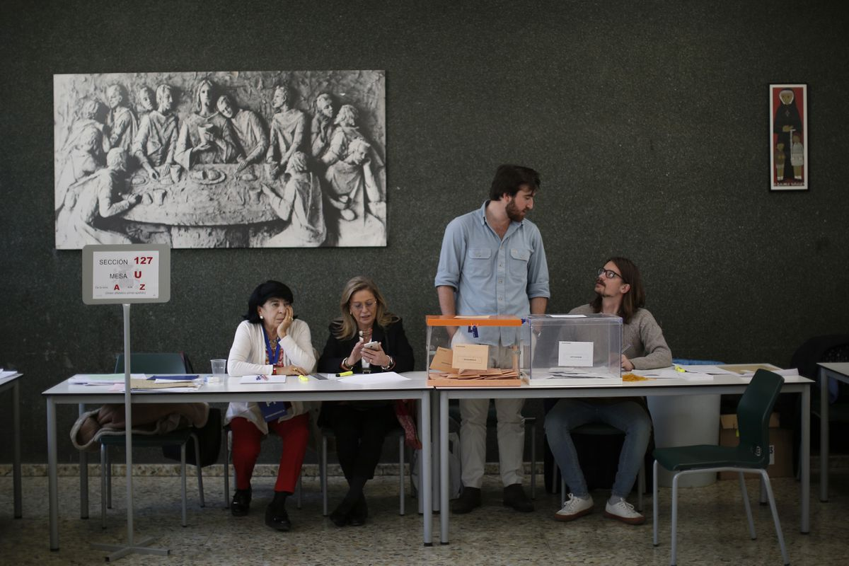 Election officials wait for voters at a polling station for the general election in Madrid, Spain, Sunday, Nov. 10, 2019. Spain holds its second national election this year after Socialist leader Pedro Sanchez failed to win support for his government in a fractured Parliament. (AP Photo/Manu Fernandez)