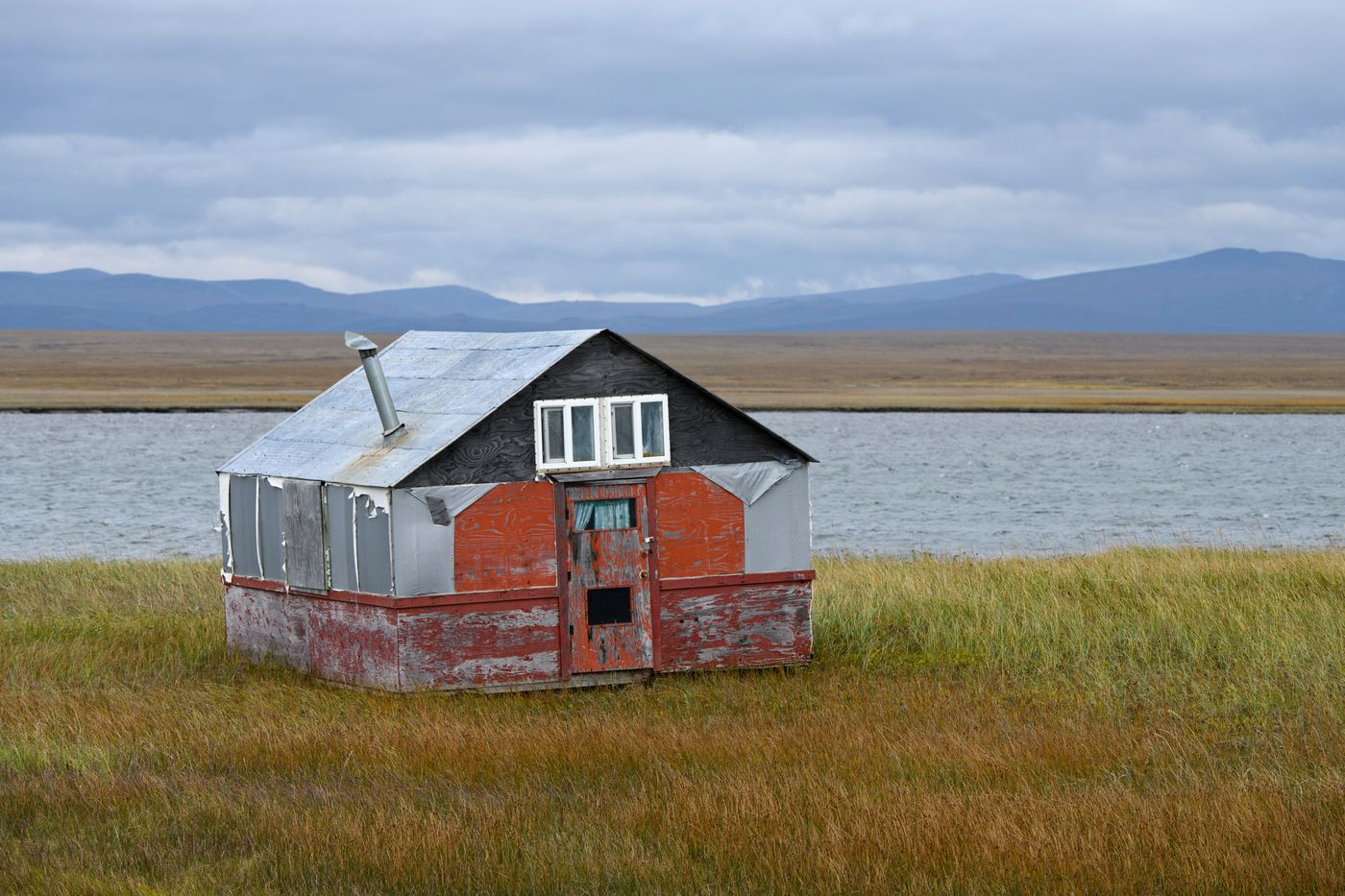 A weather-worn cabin stands along Safety Sound. (Marc Lester / ADN)