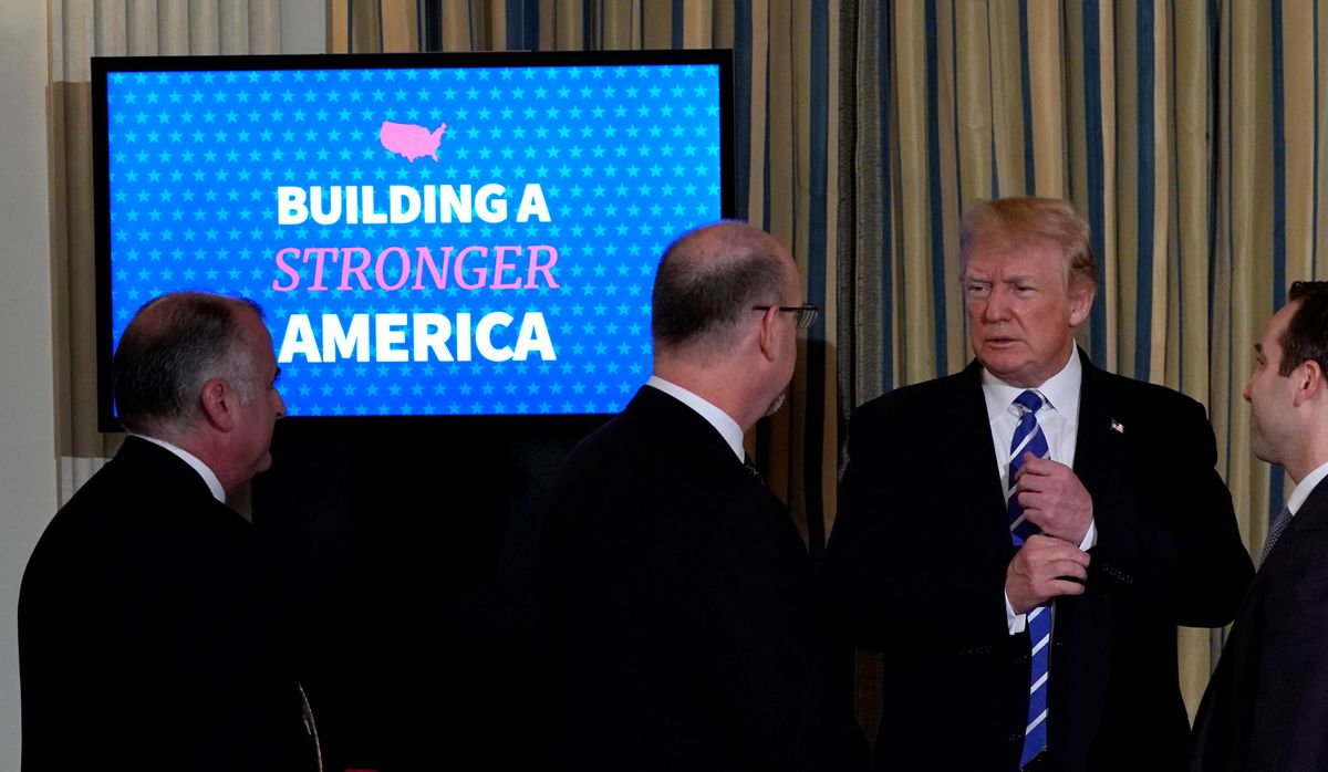 U.S. President Donald Trump speaks to attendees as he departs his infrastructure initiative meeting at the White House in Washington, U.S., February 12, 2018. REUTERS/Kevin Lamarque