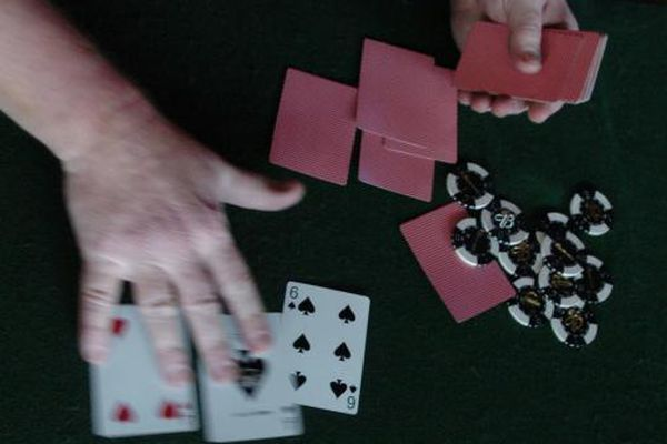 Bob Hallinen/Anchorage Daily News Stu Rosenthal deals out the first three common cards during a Texas Hold em poker tournament at the Peanut Farm. 050503