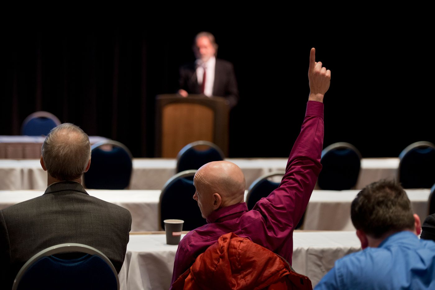 Rep. Dan Ortiz of Ketchikan asks a question of Alaska Revenue Commissioner Randy Hoffbeck during a seminar on Alaska's financial future hosted by the governor's office.