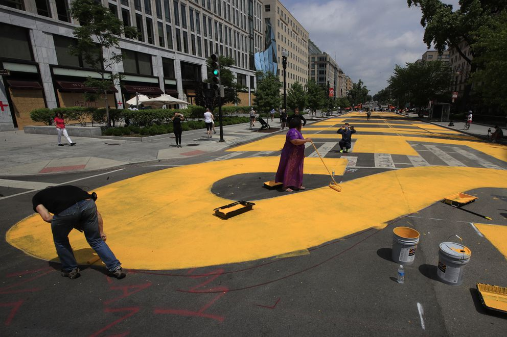 City workers and activists paint the words Black Lives Matter in enormous bright yellow letters on the the street leading to the White House, Friday, June 5, 2020, in Washington.(AP Photo/Manuel Balce Ceneta)