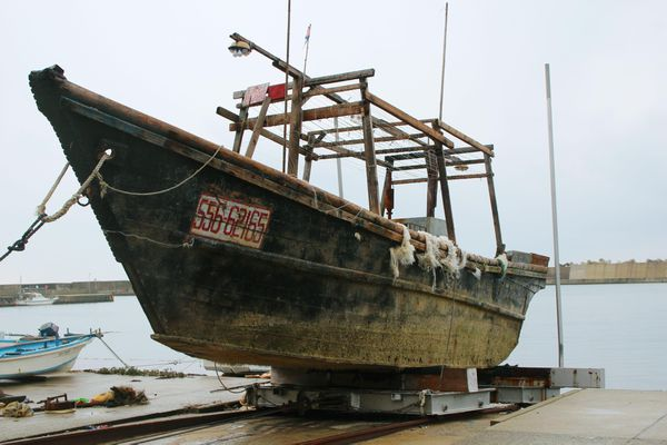 This Nov. 29, 2015 photo shows a ship of unknown nationality in Wajima, Ishikawa prefecture, central Japan, after it was found in mid-November off Noto peninsula and was towed to the shore. Japanese authorities are investigating nearly a dozen wooden boats carrying decomposing bodies found drifting off the northwestern coast over the past month. Coast Guard officials said Tuesday, Dec. 1, 2015, they have found at least 11 shoddy boats, carrying the bodies of unknown nationality since late October. They have also found fishing equipment and nets on board and signs written in Korean, suggesting they came from North Korea.