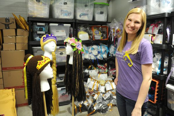Holly Christensen poses with some of the wigs made by The Magic Yarn Project in Palmer, AK on Friday, Feb. 2, 2018. Christensen is the cofounder of he organization that makes yarn wigs for young girls battling cancer. (Bob Hallinen / ADN)