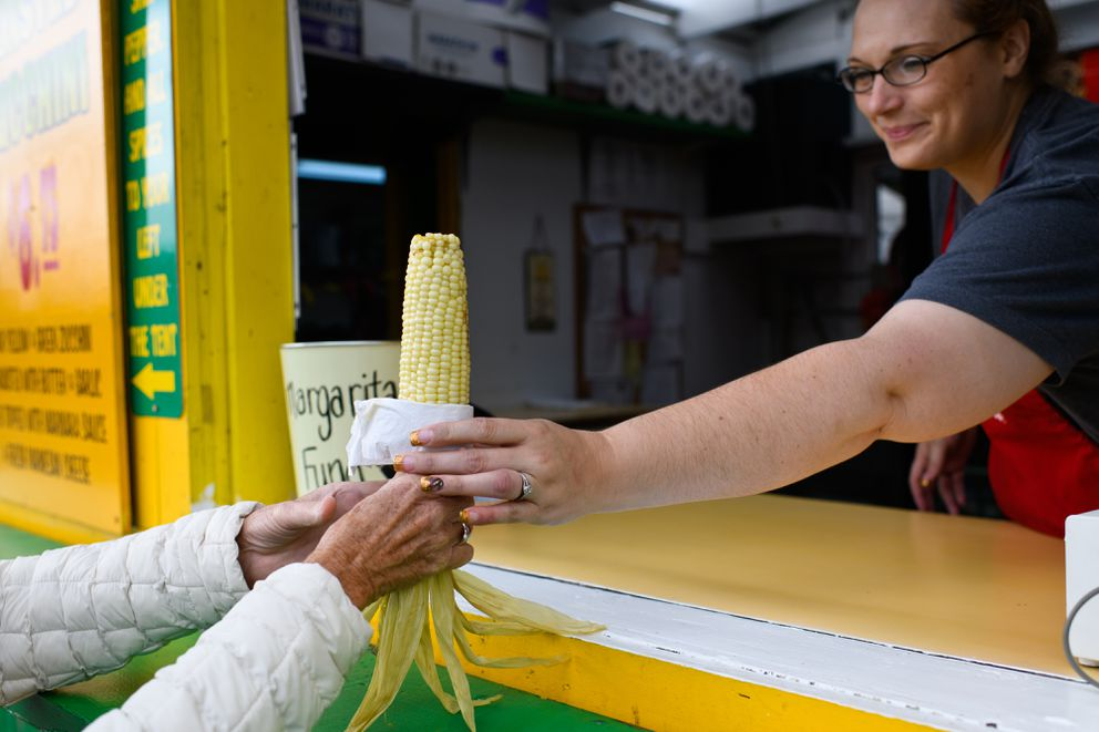 Nikki Blazka serves an ear of corn at Friar Tuck's Corn. (Marc Lester / ADN)
