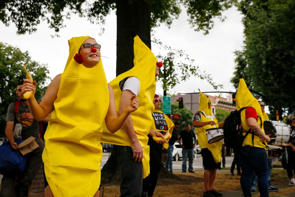 A 'Banana Bloc Dance Party ' gathering is held near Battleship Oregon Memorial Marine Park on Saturday, Aug. 17, 2019, in downtown Portland, Ore. Hundreds of far-right protesters and anti-fascist counter-demonstrators swarmed the downtown area, as police set up concrete barriers and closed streets and bridges in an effort to contain and separate the rival groups. (AP Photo/Moriah Ratner)