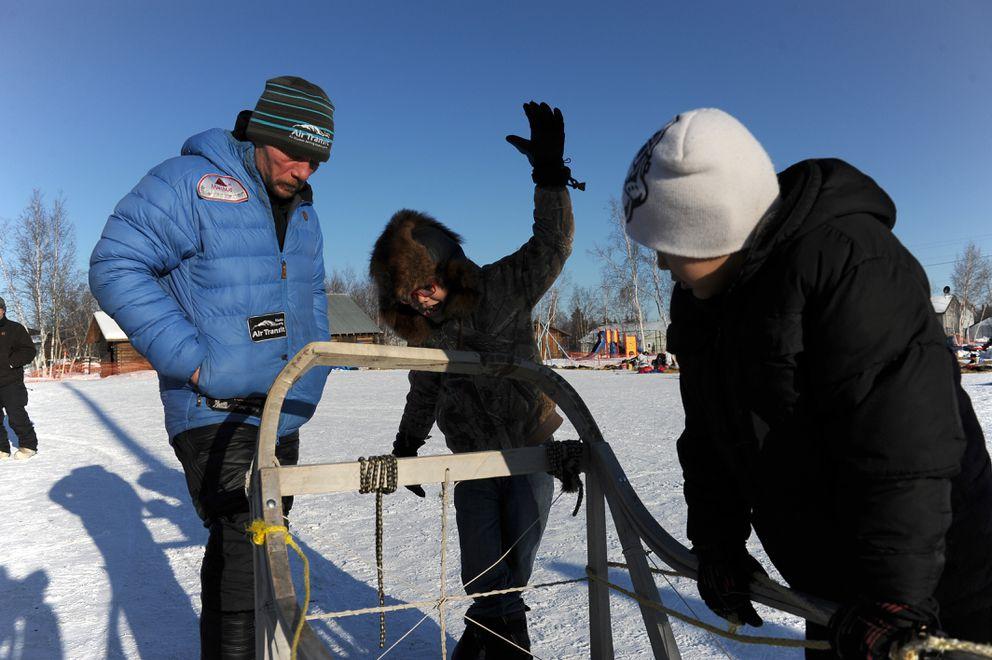 Iditarod musher Jason Mackey talks with Quincy Sam and Jan Williams about an old wooden sled near the Huslia checkpoint building on Friday. (Bob Hallinen / Alaska Dispatch News)