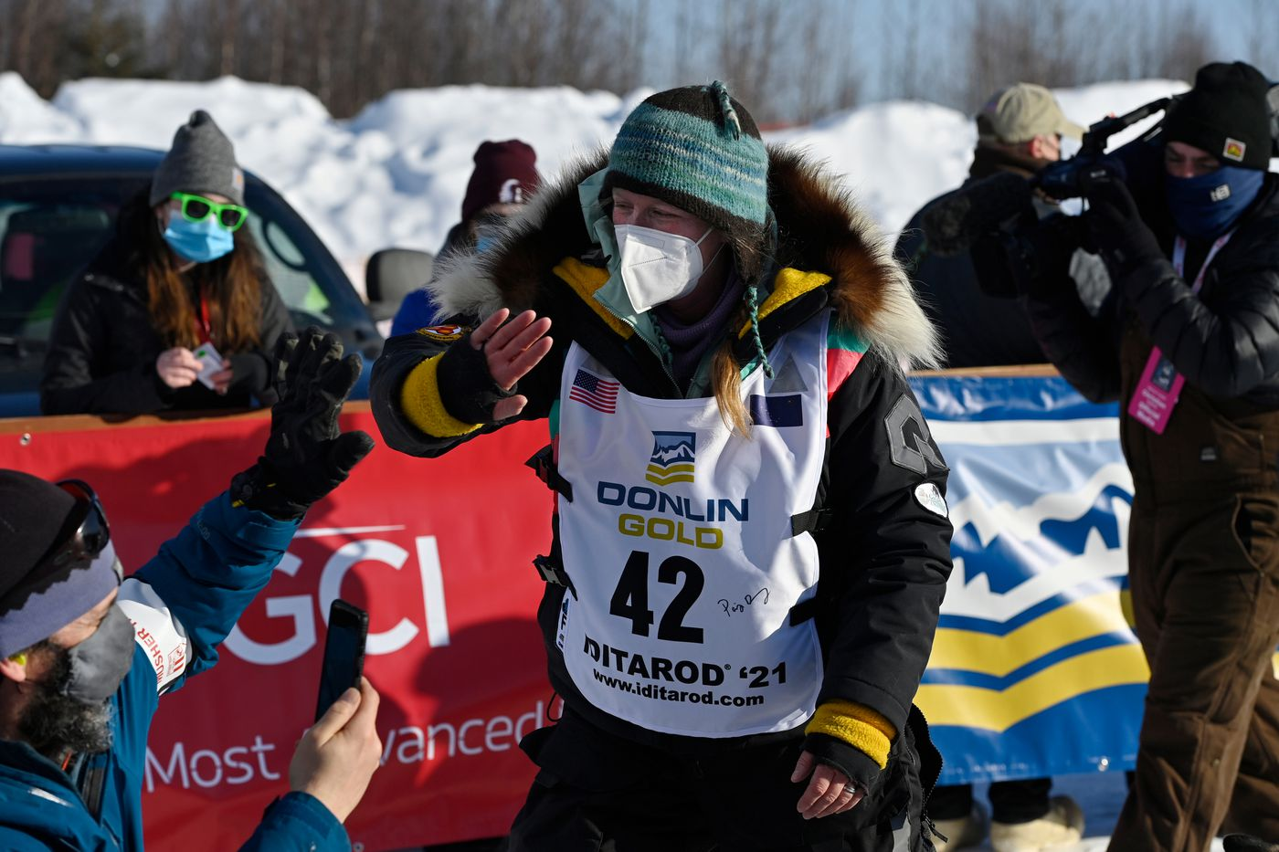 Paige Drobny high-fives people before beginning her Iditarod. Forty-six mushers began the 2021 Iditarod Trail Sled Dog race from Deshka Landing in Willow on March 7, 2021. (Marc Lester / ADN)