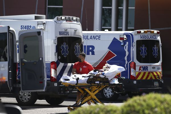 A person is brought to a medical transport vehicle from Banner Desert Medical Center as several transports and ambulances are shown parked outside the emergency room entrance, Tuesday, June 16, 2020, in Mesa, Ariz. (AP Photo/Ross D. Franklin)