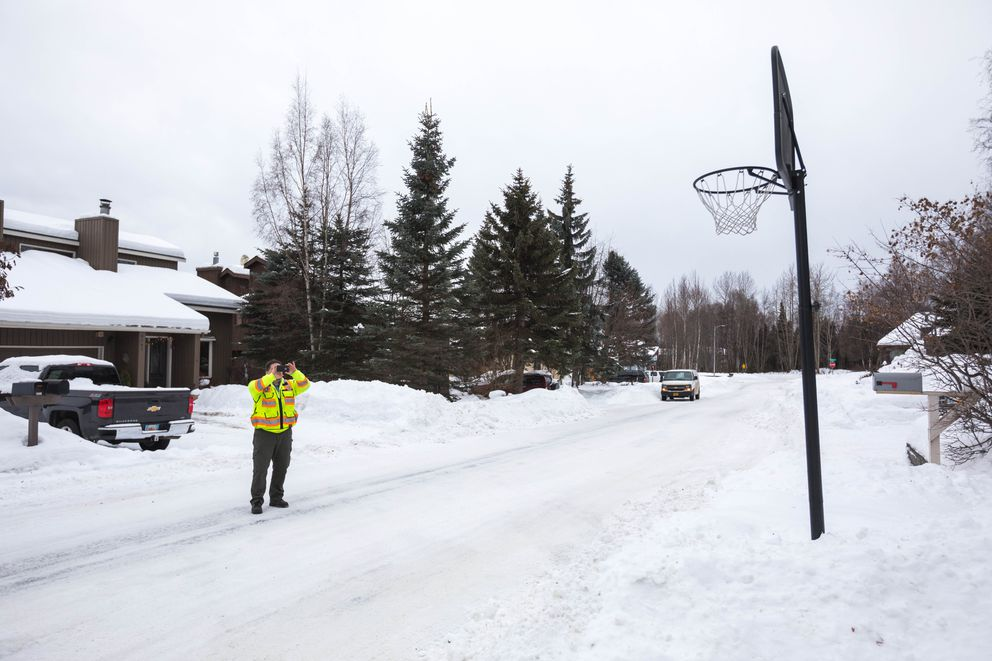 John Snelson, the Municipality of Anchorage's right-of-way enforcement lead, documents a basketball hoop that is encroaching into the road right of way near Dimond Boulevard on Tuesday. The hoop is impacting snow removal activities. (Loren Holmes / Alaska Dispatch News)