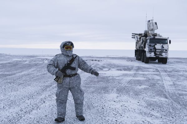 In this photo taken on Wednesday, April 3, 2019, a Russian solder stands guard as Pansyr-S1 air defense system, right, is parked on Kotelny Island, part of the New Siberian Islands archipelago located between the Laptev Sea and the East Siberian Sea, Russia. Missile launchers ply icy roads and air defense systems point menacingly into the sky at this Arctic military outpost _ a key vantage point for Russia to project power to the resource-rich polar region. Russia, has made reaffirming its presence in the Arctic the top goal. The region is believed to hold up to one-quarter of the planet's undiscovered oil and gas. (AP Photo/Vladimir Isachenkov)