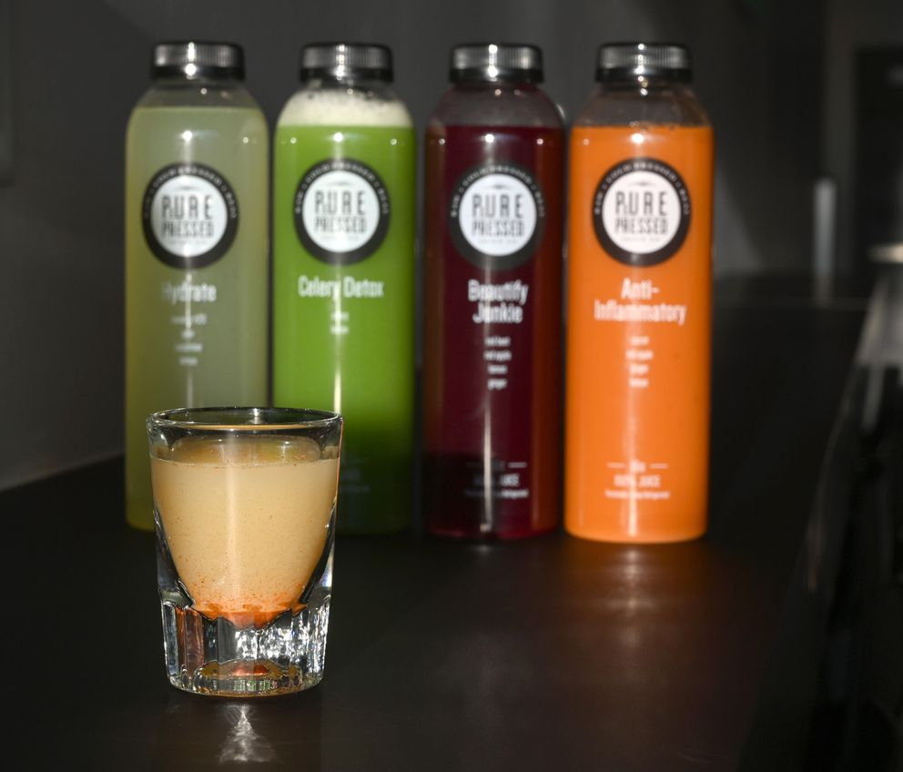 A shot of Immune Booster from Pure and Pressed Juice Co. stands in front of bottled juices. (Anne Raup / ADN)