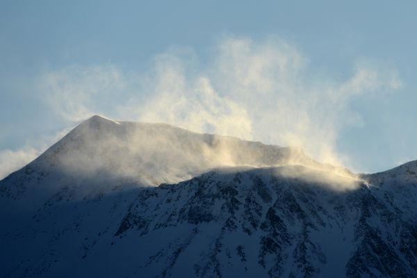 High winds blow snow off the top of Penquin Ridge near Girdwood on Monday evening, March 19, 2018. A drier weather pattern and the amount of snow this year contributes to the spindrift coming off the peaks of the Chugach and Kenai Mountains when the wind picks up. At 7 pm the National Weather Service recorded winds 0f 15 mph with gusts to 36 mph atop Penquin Peak.