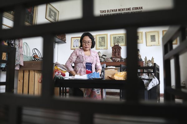 Parahita Satiti, who hopes to get extra income after her office cut her monthly allowance by half during the COVID-19 pandemic, arranges traditional Javanese women's clothings she made in Jakarta, Indonesia, Thursday, Nov. 26, 2020. Satiti is one of dozens of tenants who joined online events run by Omah Wulangreh, an art and cultural community in Jakarta that provides online space for sellers and for buyers to preorder items like traditional snacks, batik clothes, or coffee. (AP Photo/Achmad Ibrahim)