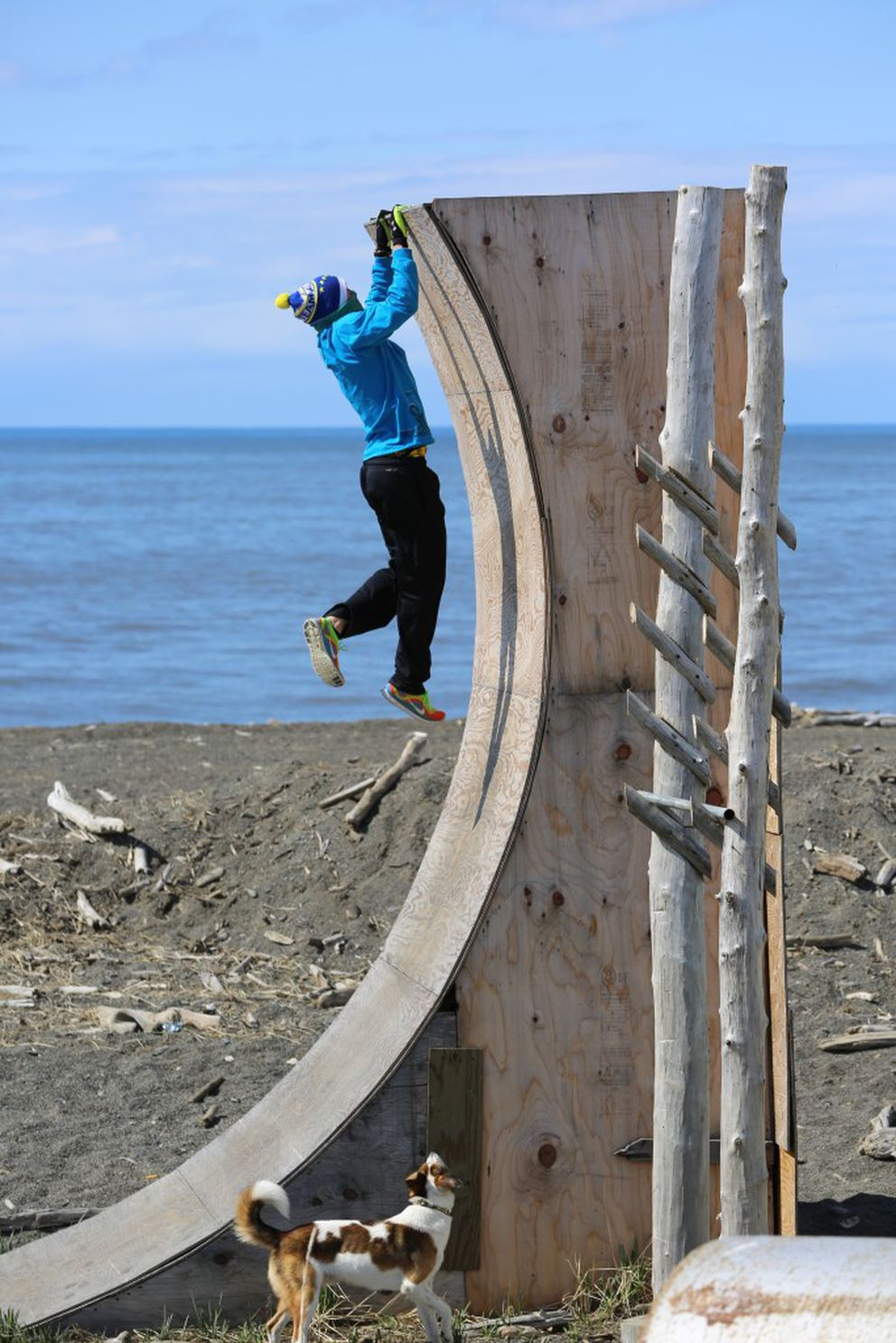 Nick Hanson of Unalakleet works out in May 2015 on his obstacle course. His dog Snapchat watches as Hanson hangs off the top of the warped wall. (Bret Hanson)