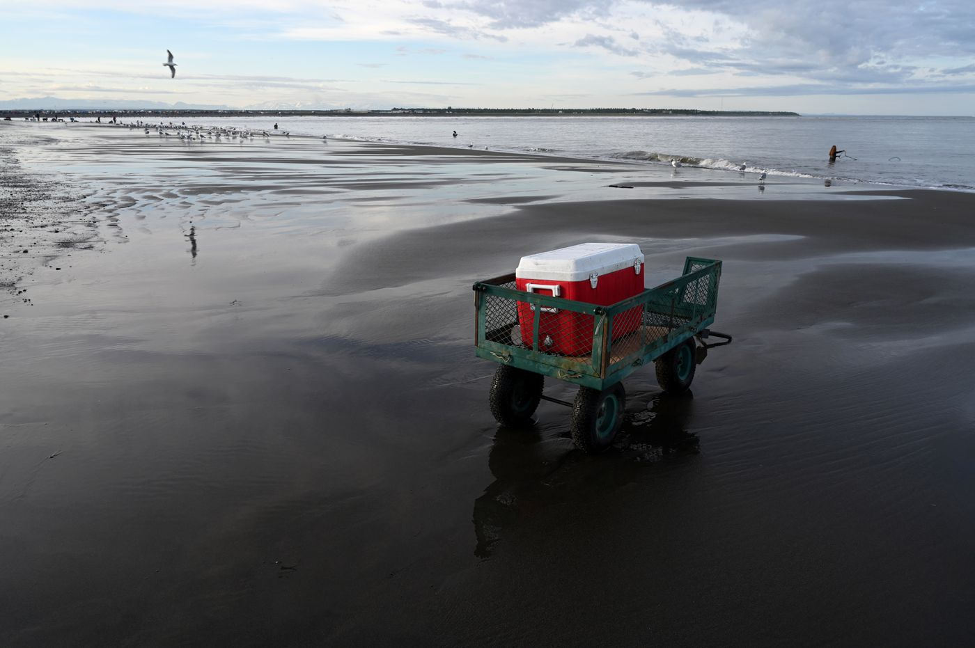 Early July 21, 2020, the beach at the Kenai River was fairly quiet. A cart and cooler wait for dipnetters to bring salmon. (Anne Raup / ADN)