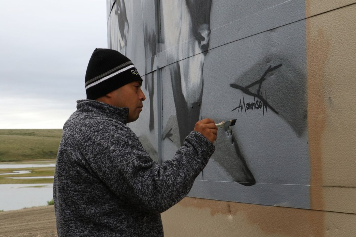 Artist Andrew Morrison signs the newest Water is Life mural in Deering, Alaska. (Photo by Bailey Berg / Alaska Dispatch News)