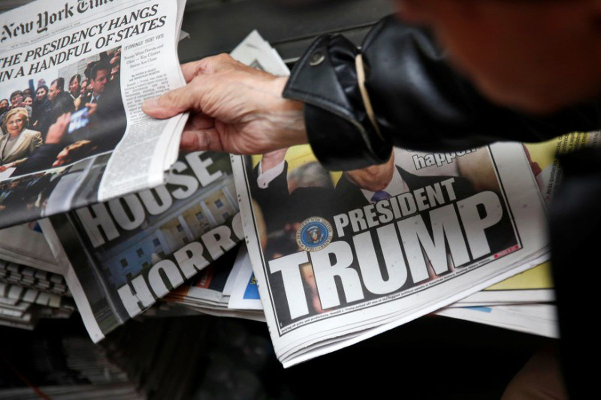 A man hands a newspaper to a customer at a news stand in New York, U.S., November 9, 2016. REUTERS/Shannon Stapleton