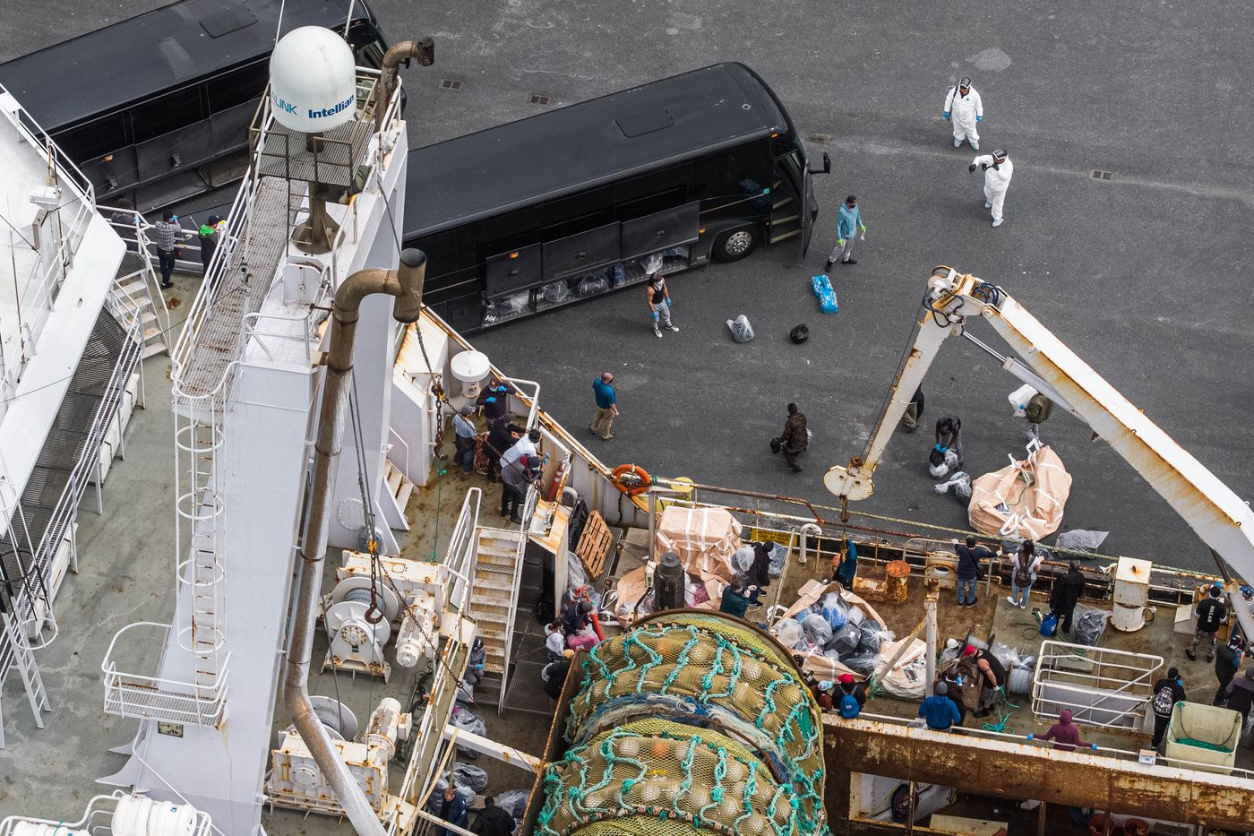 JULY 22. Crew disembark from the American Triumph and board busses in Seward. American Seafoods, which operates the factory trawler, reported over the weekend that 85 crew members tested positive for COVID-19. The crew disembarked in Seward and will be transported to Anchorage where they will be isolated for further care. (Loren Holmes / ADN)