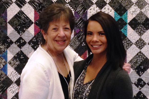 Debby Hudson poses in 2017 in front of a quilt she made with AmberJones. Hudson helped Jones as a Court Appointed Special Advocate whenJones was an infant. For the last 22 years, Hudson has organized a quiltauction to raise money for the program. This year the auction takesplace at 11am on Saturday, November 22, at the University Center inAnchorage. (Photo courtesy of Debby Hudson)