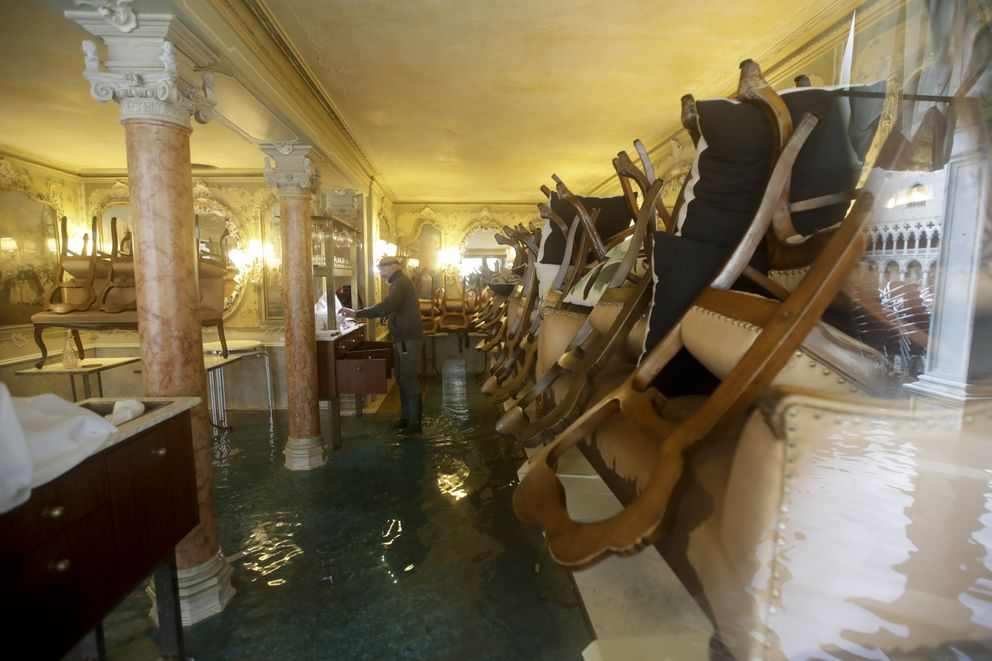A man stands in his shop flooded with water, in Venice, Wednesday, Nov. 13, 2019. The high-water mark hit 187 centimeters (74 inches) late Tuesday, Nov. 12, 2019, meaning more than 85% of the city was flooded. The highest level ever recorded was 194 centimeters (76 inches) during infamous flooding in 1966. (AP Photo/Luca Bruno)