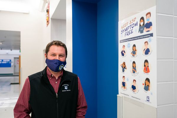 Creekside Park Elementary principal David Christal stands next to a COVID-19 poster on Friday, Jan. 15, 2021 at the school. The school is preparing for the return of in-person learning on Tuesday, Jan. 19. (Loren Holmes / ADN)