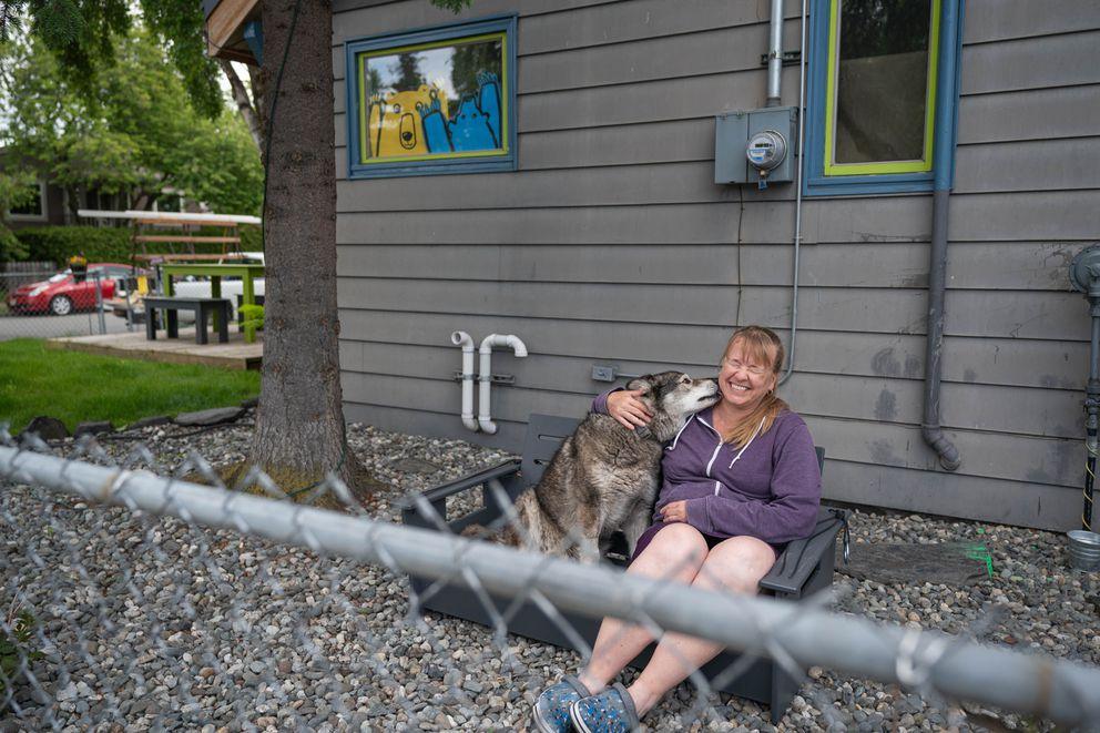 Linda Klinkhart sits with her neighbor Tonio Nguyen's dog Newtok on Wednesday, June 17, 2020 in South Addition. (Loren Holmes / ADN)