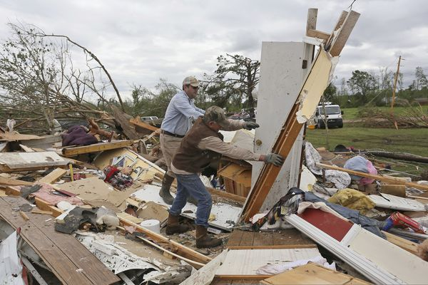 Roman Brown, left and Sam Crawford, right move part of a wall out of their way Sunday, April 14, 2019, as they help a friend look for their medicine in their destroyed home along Seely Drive outside of Hamilton, Miss. after an apparent tornado touched down Saturday night, April, 13, 2019. (AP Photo/Jim Lytle)