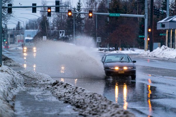 Vehicles drive through standing water on 36th Avenue in Midtown Anchorage on Monday, Jan. 18, 2021. (Loren Holmes / ADN)