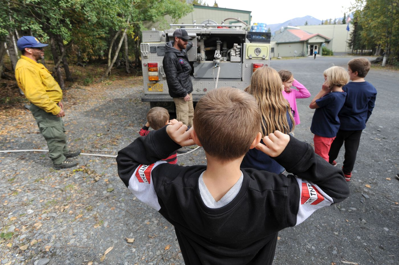 Students at Cooper Landing school get a demonstration of a fire truck Sept. 6, 2019. The group of firefighters visited the school to help the children understand the equipment and the efforts to fight the Swan Lake fire. (Anne Raup / ADN)